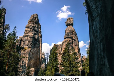 "Photo taken in the valley of a rock city in the Czech Republic with two rocks called ""starost and starost's wife"" with a blue sky with some cluds in the background."