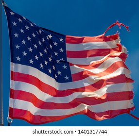 photo of a tattered American flag blowing in the wind against