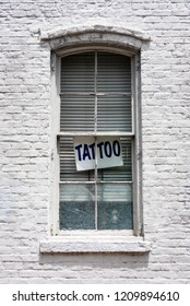 A photo of a tattoo sign in a window of a white brick building.