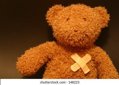 Photo of a teddy bear with a baid aid over his heart.