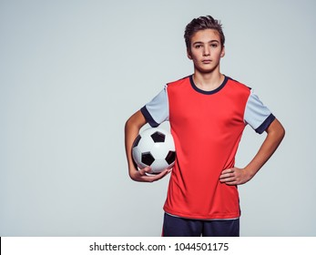 Photo of teen boy in sportswear holding soccer ball - posing at studio