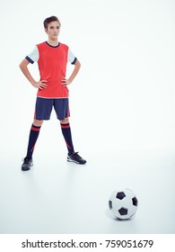 Photo of teen boy in sportswear holding soccer ball - posing at studio. Full portrait.