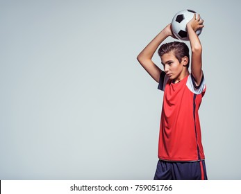 Photo of teen boy in sportswear holding soccer ball over the head - posing at studio