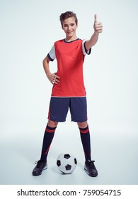 Photo of teen boy in sportswear holding soccer ball and hand thumb up gesture - posing at studio. Full portrait.