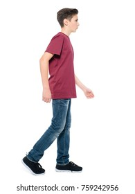 Photo of teen boy walking at studio over white background. Profile portrait