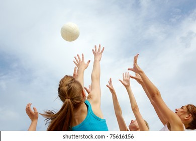 Photo of teenage friends playing with ball on background of cloudy sky