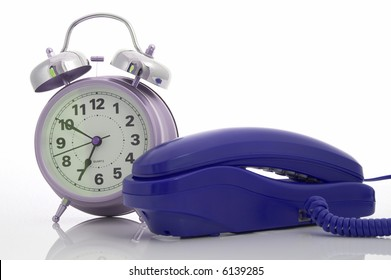 Photo of a telephone and an alarm clock over a white background