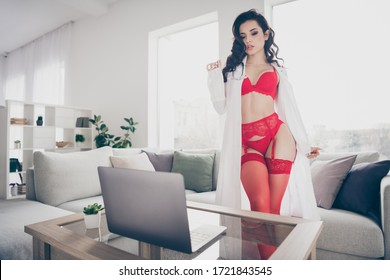 Photo of tempting slim lady work home private online notebook chat undressing nude body play naughty lover nurse role take off lab coat look live screen flirty eyes wear red bikini tights room indoors