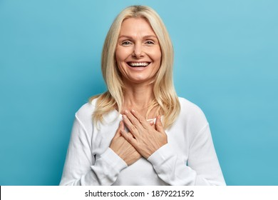 Photo of tender blonde woman with wrinkles and blonde hair keeps hands pressed to chest being sincerely thankful for good supporitve words smiles gently wears casual white jumper isolated on blue