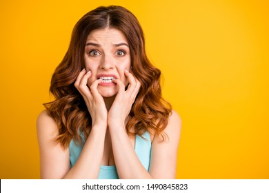 Photo of terrible feared girlfriend driven mad with some sorrow happened to her biting nails with panic while wearing teal tank-top isolated with yellow vivid color background