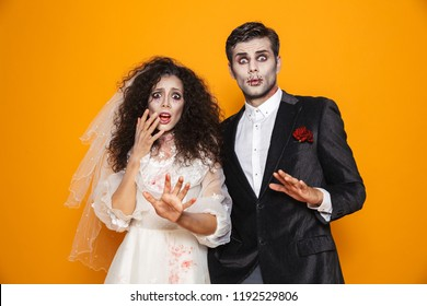 Photo of terrifying zombie couple bridegroom and bride wearing wedding outfit and halloween makeup scaring you isolated over yellow background