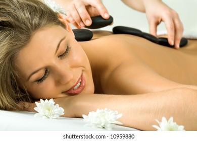 Photo of therapist putting the hot stones on the back of woman