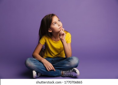 Photo of thinking cute girl looking upward while sitting on floor isolated over purple background