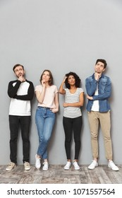 Photo of thinking group of friends standing isolated over grey wall background looking aside.