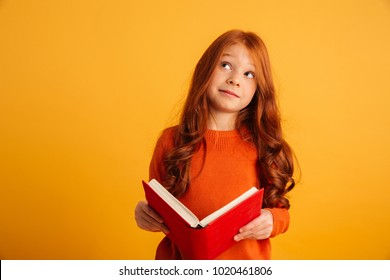 9f433744300 Photo of thinking little redhead girl with freckles standing isolated over  yellow background reading book.