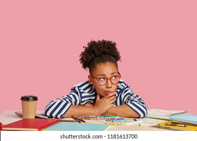 Photo of thoughtful girl multiplier considers about creative ideas, during working process, leans at table with markers, diary, takeaway coffee, look pensively aside, isolated over pink background