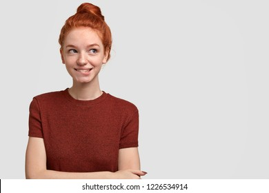 Photo of thoughtful tender woman bites lower lip, looks with dreamy expression aside, has ginger hair combed in knot, keeps hands crossed over chest, stands against white wall with free space for text