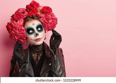 Photo of thoughtful woman with halloween makeup, dressed in black traditional outfit, prepares to celebrate Day of Death and remember died relatives during these two days in November. Mexican party