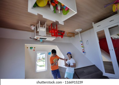 Photo of Three asian kids in the strange up side down house musuem in Pattaya Rayong, Thailand December 25, 2018