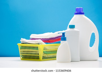 Photo of three bottles of detergent and yellow basket with towels on empty blue background