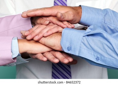 Photo of three business people stacking hands to represent teamwork.