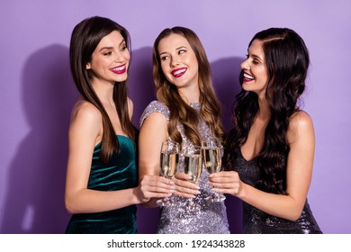 Photo of three cheerful ladies hold glasses toast look each other wear fancy dresses isolated purple color background