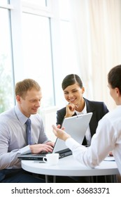 Photo of three confident employees planning work around table
