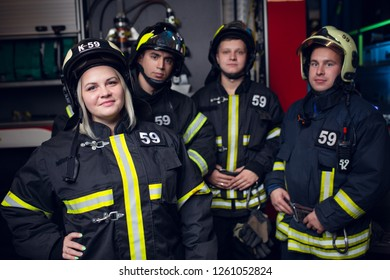 Photo of three firemen men and smiling woman on background of fire truck