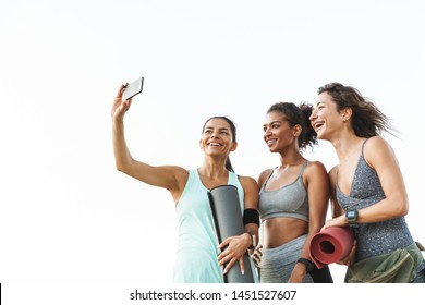 Photo of three joyful multiethnic sportswomen in tracksuits smiling and taking selfie on cellphone while standing over white wall outdoors
