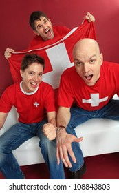Photo of three male Swiss sports fans cheering for their team.