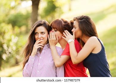 Photo of three whispering woman