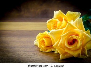 Photo Of Three Yellow Roses On Wood Table Background