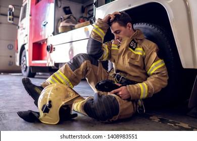 Photo of tired fireman sitting on floor near fire truck