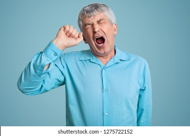 Photo of tired grey haired retired man feels sleepy, yawns as feels tired, opens mouth widely, dressed in elegant shirt, poses over blue background. Monochrome. Tiredness and pension concept