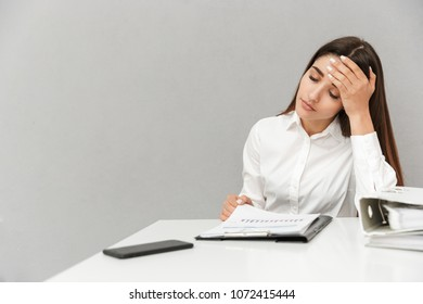 Photo of tired woman in white shirt sitting at table with lots of document folders and propping her head isolated over gray background