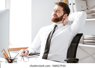 Photo of tired young businessman sitting in office while stretching.