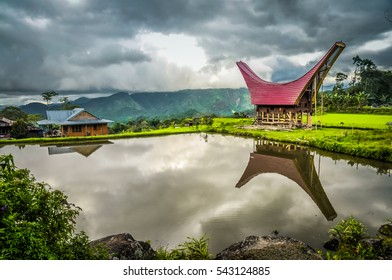 Photo of tongkonan and house near lake with view on mountains in distance in Toraja region in Sulwesi, Indonesia.