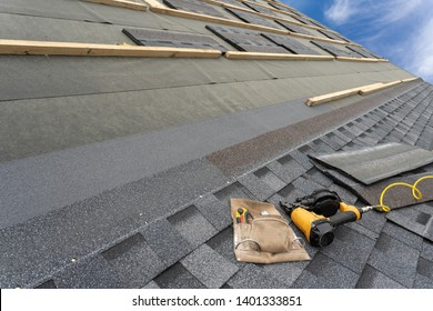 Photo of toolbelt on layer of asphalt or bitumen shingle on top of the new roof under construction residential house or building