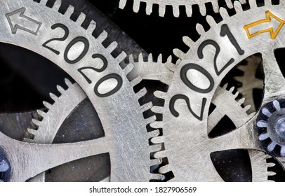 Photo of tooth wheel mechanism with numbers 2021 and 2020 imprinted on metal surface. New Year concept.