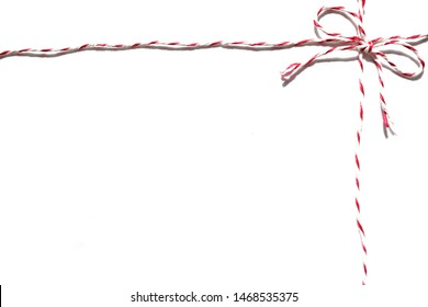 Photo of top right corner border formed by red and white postal string with bow loop isolated on white background with blank copy space for text poem haiku or note