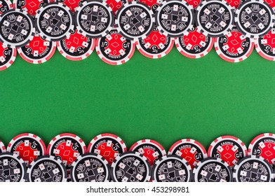 photo of top view of green casino table with red and black chips