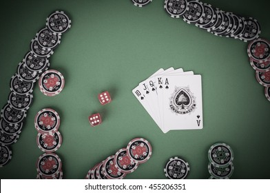 photo of top view of green casino table with royal flush, red and black chips - vintage