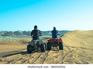 Photo of the tourist enjoys riding a bike in the desert sand dune.