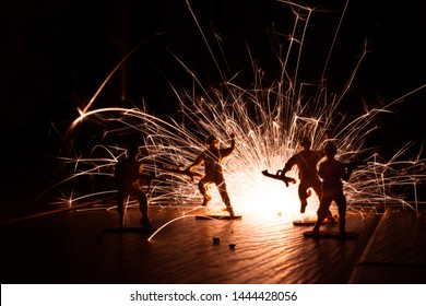 A photo of toy soldiers with a sparkler behind them simulating an explosion. Two of the soldiers appears as if they are jumping away from the explosion. This is a low light silhouette picture.