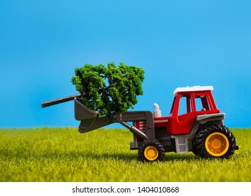 Photo of a toy tracktor standing with tree on grass surface on blue background.