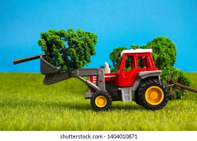 Photo of a toy tracktor standing with trees on grass surface on blue background profile view.