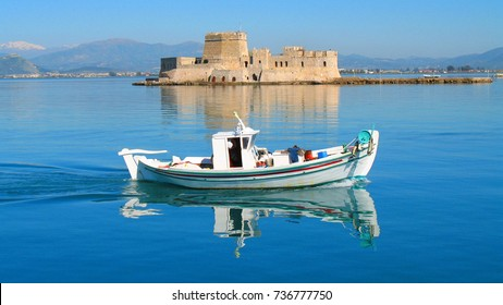 Photo of traditional fishing boat and Bourtzi fortress as background in picturesque city of Nafplio former capital of Greece, Argolida, Peloponnese