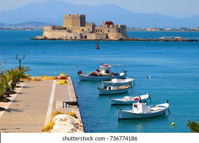 Photo of traditional fishing boats and Bourtzi fortress in picturesque city of Nafplio former capital of Greece, Argolida, Peloponnese