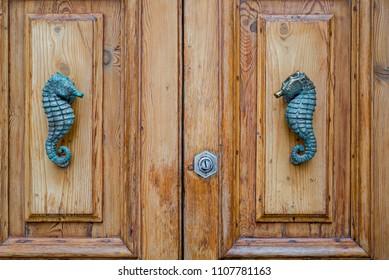 Photo of Traditional metal seahorse door handle on wooden door, Malta