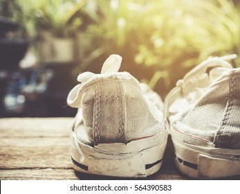 Photo of travel concept. White sneakers shoes on wooden background with copy space. Vintage style image.